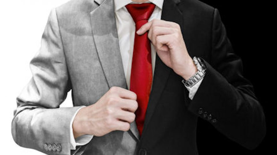 Businessman in white and black suit tying red necktie, isolated on white and black background